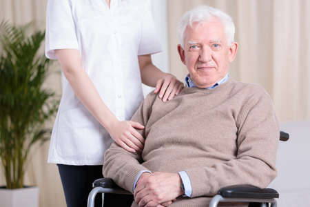 color therapist: Elderly smiling man on wheelchair and his nurse