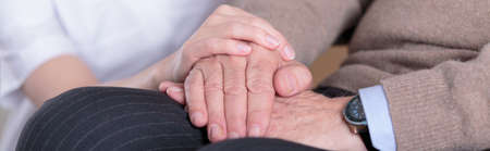 hospital care: Close-up of nurse holding aged mans hands Stock Photo