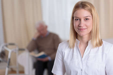 carer: Portrait of young attractive smiling nurse in duster
