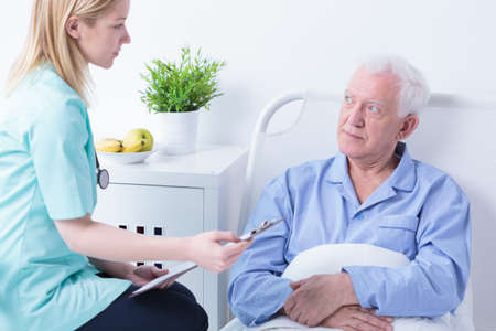 medical history: Experienced young nurse checking senior patients medical history