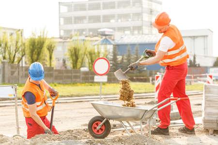 albañil: Constructores que trabajan duro verter suelo en carretilla