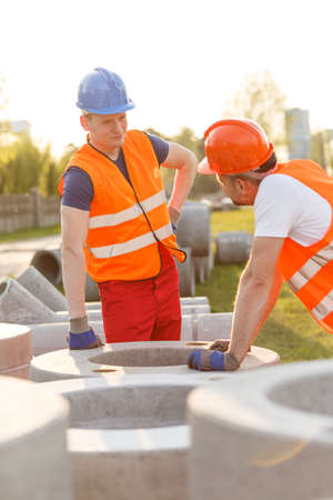 speaking tube: Tired construction workers having small talk at work Stock Photo