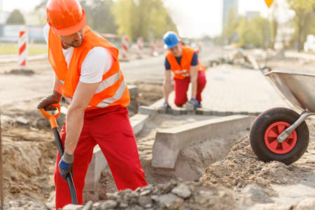 trabajando duro: Dos constructores que trabajan duro en uniformes poniendo pavimento Foto de archivo