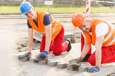 Twee glimlachende bouwvakkers leggen van nieuwe kasseien