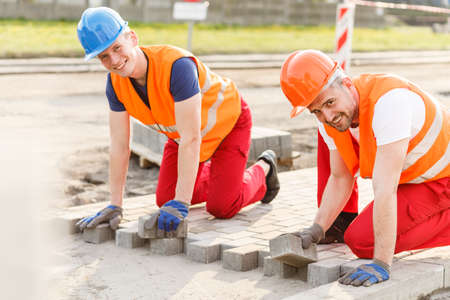 Two smiling construction workers laying new cobblestones