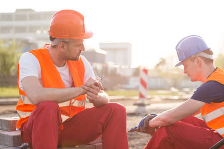 road worker: Two exhausted builders and rest during work Stock Photo