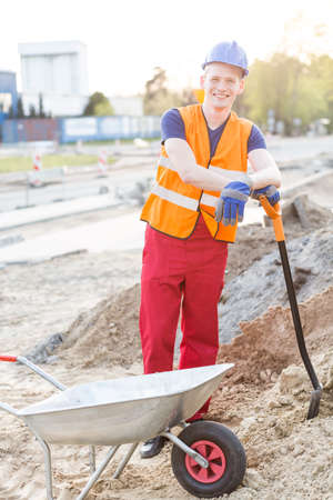 exhausted worker: Young happy construction worker leaning on shovel