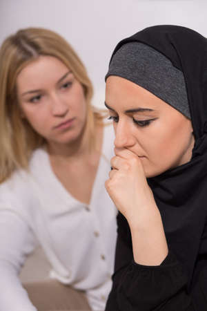 arab girl: Despair muslim woman meeting with tolerant friend