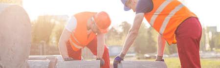 重いコンクリート ブロックに移動する 2 つの強力な建設