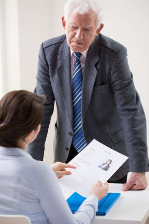 irate: Woman showing her resume to irate manager Stock Photo