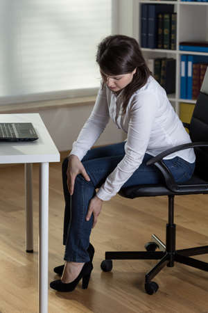 Office worker massaging aching legs Stock Photo