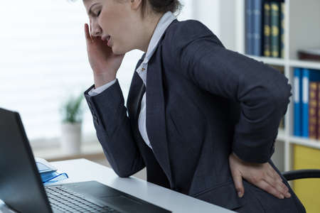 overloading: Women with problem with spine at office work Stock Photo