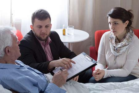 Senior terminally ill father signing his last will Standard-Bild