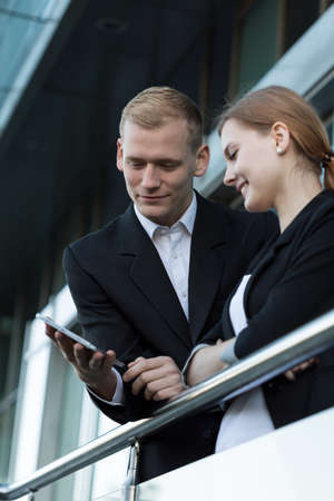 fellow: Fellow workers using phone during break, vertical Stock Photo