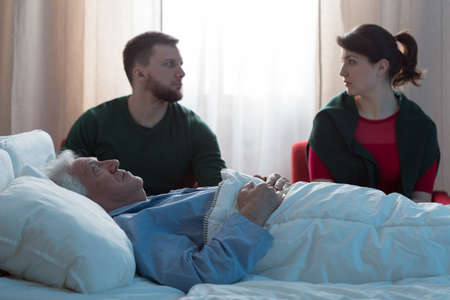 deceased: Two adults guarding by deceased father in hospital Stock Photo