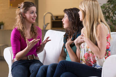 Talking with girl friends in living room on weekend afternoon Фото со стока