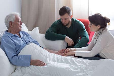 支持の成人した子供とベッドで末期のパパ 写真素材