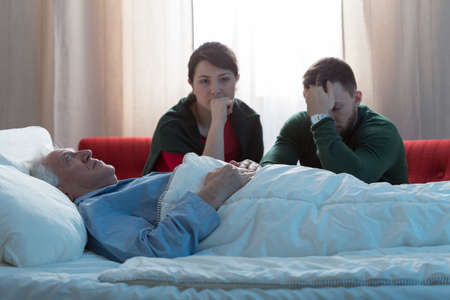 rest in peace: Adult siblings crying after their dead father Stock Photo