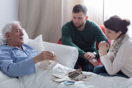 relatives: Older sick man in hospital opening old letters Stock Photo
