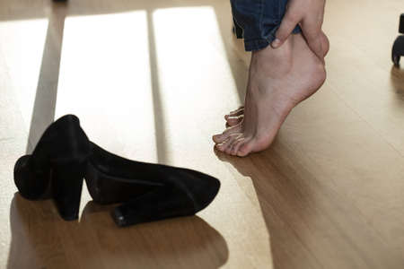 hard day at the office: Aching feet after whole day in high heels at office Stock Photo