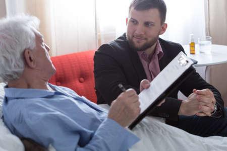 Stervende man ondertekening van zijn testament in het bijzijn van notaris Stockfoto