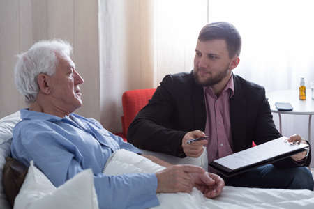 inheritance: Older dying man in hospital talking with his notary