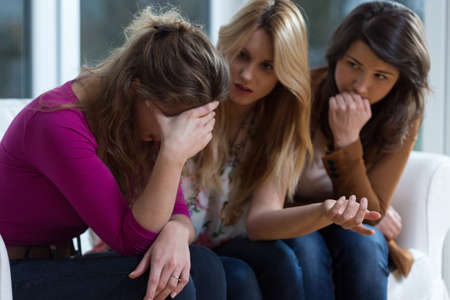 difficulties: Sad girl and supporting friends trying to solve a problem Stock Photo