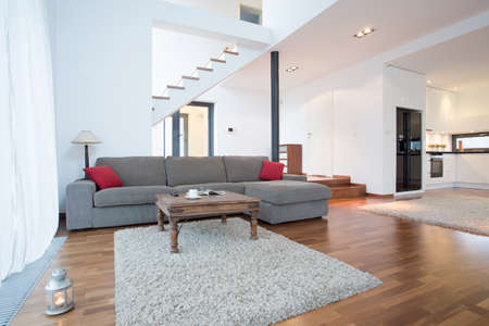 Grijze bank met rode kussens in de woonkamer
