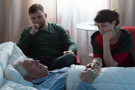 Young worried daughter sitting with her terminally ill father
