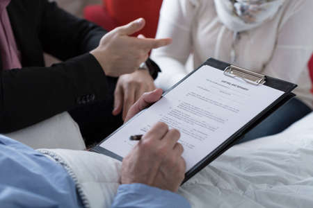 Close-up of older sick man holding his last will and testament Archivio Fotografico