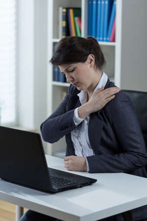 overloading: Overworked women feels arm pain in the office Stock Photo