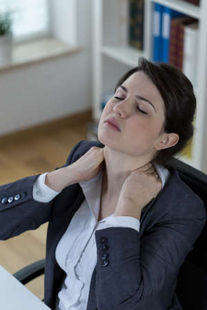 overloading: Tired women with neck ache at work