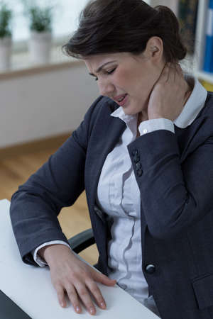 overloading: Overworked businesswomen suffer from neck pain Stock Photo