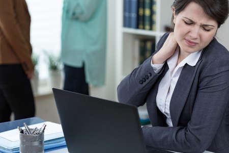 Office worker suffering from painful tense neck muscles Stock Photo