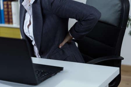 dolor de espalda: Empleado de oficina con dolor de espalda después de mucho trabajo frente a la computadora