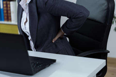 Office worker with backache after long work in front of computer Stock Photo