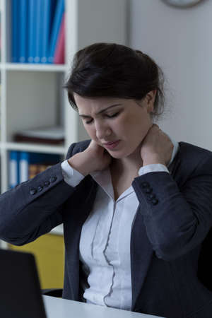muscle tension: Worker suffering from neck ache at office Stock Photo