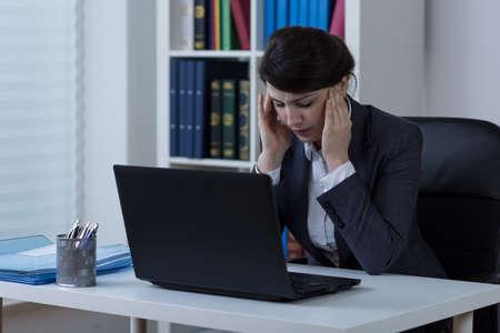 overloading: Businesswomen with headache during work