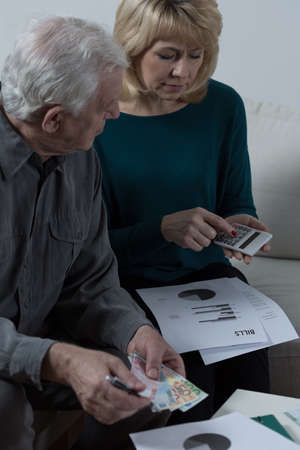 Elderly couple sitting and discussing financial problems photo