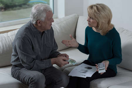 people problems: Old couple sitting on a sofa and talking about money