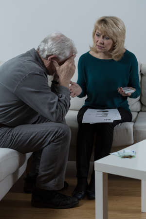 financial problems: Old couple sitting by the table and discussing financial problems Stock Photo