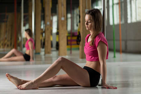 pole dance: Girl sitting on the floor in pole dance class Stock Photo