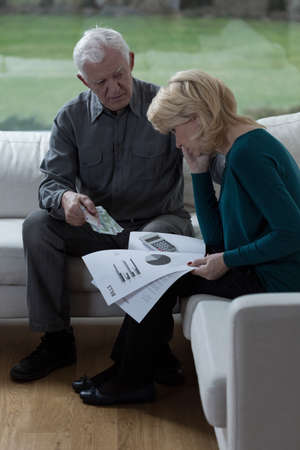 Old marriage talking about bills and their financial situation photo