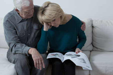 couple on couch: Elderly marriage is worried about their high bills Stock Photo