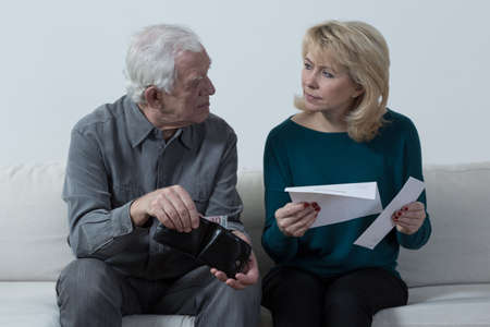 Old couple with financial difficulties siting on a sofa photo
