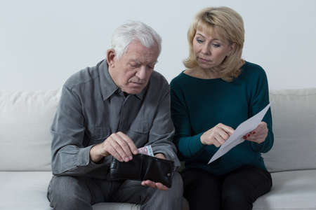 Elderly marriage sitting and discussing their financial problems Stock Photo