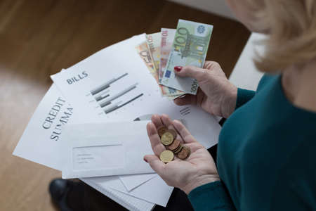 difficulties: Elderly woman counting money and solving financial difficulties