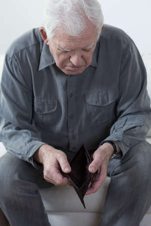 empty wallet: Old man sitting on a couch and looking at an empty wallet