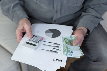 difficulties: Old man with financial difficulties holding bills Stock Photo