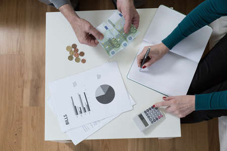 financial problems: Sitting at a wooden table and solving financial problems